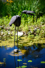 Metal Birds On Long Legs, Which Open The Beak After The Flow Of Water In The Pond.