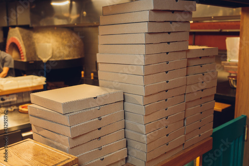 Pizzas cardboard boxes for shipping and delivery. a lot of packaging is on the kitchen stock. - fototapety na wymiar