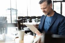 Businessman Using Digital Tablet At Restaurant Table