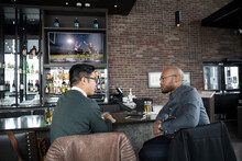 Businessmen Talking, Drinking Beer And Watching Game At Sports Bar