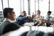 Business People Toasting Beer And Water Glasses In Restaurant