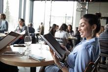 Smiling Woman Looking At Menu In Restaurant