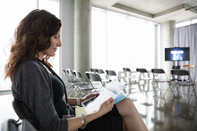 Dedicated Businesswoman Reading Paperwork, Waiting In Conference Audie