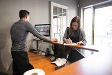 Woman Filling Out Registration Paperwork At Gym Front Desk
