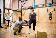 Personal Trainer Guiding Client Doing Box Step Ups In Gym
