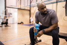 Man With Water Bottle Taking A Break From Workout In Gym