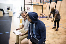 Personal Trainer And Client With Clipboard In Gym