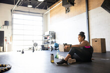 Young Woman Taking A Break From Workout On Floor In Cross Training Gym