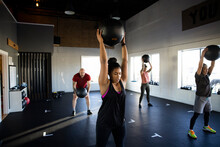 Group Fitness Class Doing Medicine Ball Lifts In Gym Studio