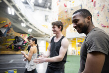 Happy Young Male Climbers Chalking Up Hands In Climbing Gym