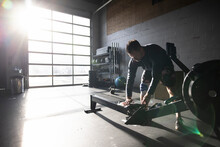 Man Wiping Down Rowing Machine In Sunny Cross Training Gym