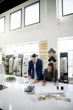 Interior Designers Working On Blueprint In Showroom Office
