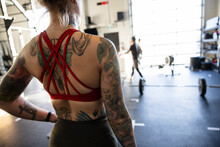 Close Up Athletic Woman With Back Tattoos In Sports Bra In Gym