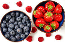 Blueberries And Strawberries In Blue Bowls With Raspberries On A White Background.