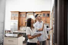 Couple Choosing Lever Handles In Kitchen Showroom