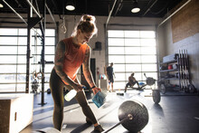 Woman Disinfecting Barbell With Spray Cleaner And Cloth In Sunny Gym