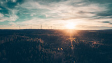 Cinematic Aerial View Of Wind Turbines In The Forest. Warm Teal And Orange Look. Panorama Format.