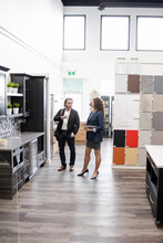 Saleswoman And Customer Talking In Kitchen Showroom