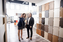 Saleswoman Showing Colors Of Cabinet To Customer In Kitchen Showroom
