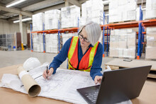 Architect Working On Blueprint In Distribution Warehouse