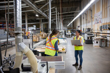 Colleagues Discussing Work With Laptop In Distribution Warehouse