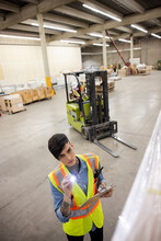 Worker Inspecting Cargoes In Distribution Warehouse