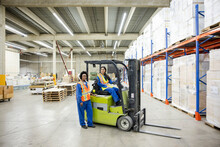 Portrait Of Forklift Driver And Worker In Distribution Warehouse