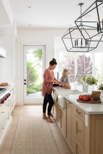 Mother And Daughter Slicing Bread In Luxury Home Kitchen