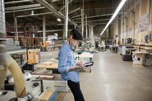 Supervisor Using Digital Tablet In Distribution Warehouse