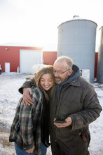 Portrait Of Father And Daughter Outside Dairy Farm