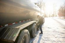 Driver Checking Tires Of Milk Tanker Truck