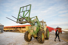 Farmers Working With Tractor On Farmyard