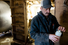 Worker Holding Bottle Of Medication In Barn