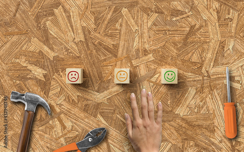 hand reaching out to cubes with smiley symbols surrounded by handyman tools on wooden background - fototapety na wymiar