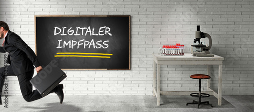 running businessman with suitcase in front of a blackboard with German message for DIGITAL VACCINATION PASSPORT on a brick wall - fototapety na wymiar