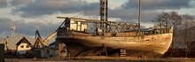 Old Wooden Ship (fishing Boat) Standing On Land In A Harbor At Sunset. Baltic Sea, Latvia. Soft Sunlight, Dramatic Sky. Industry, Business, Transportation, Service, Logistics, Shipping, History, Past