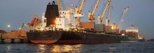 Large Cargo Ship Anchored In Illuminated Riga Port, Latvia, At Night, Close-up. Freight Transportation, Global Communications, Logistics, Environmental Damage Theme