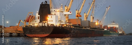 Fototapeta Large cargo ship anchored in illuminated Riga port, Latvia, at night, close-up. Freight transportation, global communications, logistics, environmental damage theme obraz