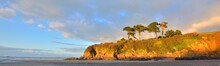 Orange Cliff With Tall Trees On The Coast Of Bay Of Douarnenez. Blue Sky With Colorful Evening Clouds. Reflections On The Water. Brittany, France