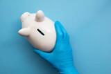 Fototapeta Kawa jest smaczna - Doctor wearing blue gloves holding a piggy bank. Health care finance concept