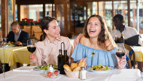 Obraz Two girls are discussing something fun at a table in a restaurant - fototapety do salonu