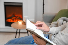 Young Man Reading Book Near Fireplace At Home
