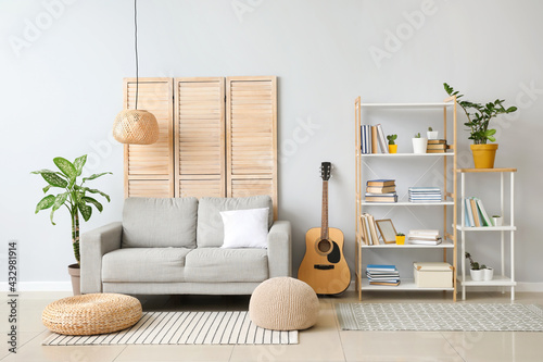 Interior of modern living room with shelf unit and sofa - fototapety na wymiar