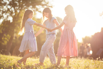 Dancing and be happy. Three little girls together in nature.
