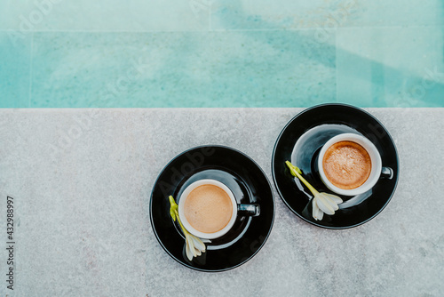 Coffee in espresso cups for two people on luxury pool side on vacation. High end resort hotel. Top view of mugs. - fototapety na wymiar