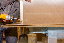 Carpenter Uses Hand Drill, Acu Power Tool And Tightens The Screws On The Wooden Door Frame.