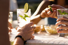 Hands Holding A Fresh Alcoholic Long Drink Cocktail On A Table. Gathering Of Friends In An Outdoor Pub In The Summer.