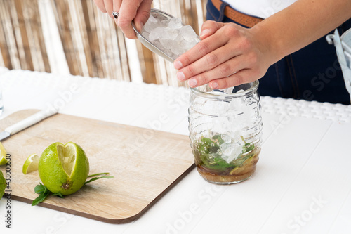 Obraz Bartender putting ice cube into shaker while making fresh cocktail with lime juice - fototapety do salonu