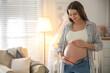Leinwandbild Motiv Happy pregnant woman touching her belly indoors