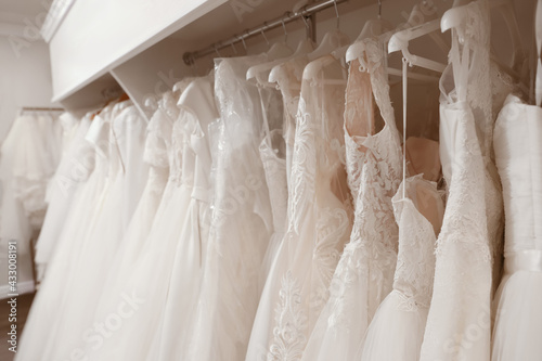Different wedding dresses on hangers in boutique - fototapety na wymiar
